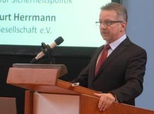 Ein Mann in einem Anzug steht an einem Rednerpult und spricht in ein Mikrofon.