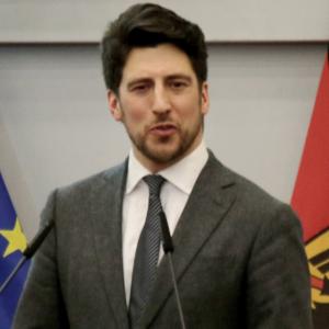 Ein Mann im Anzug steht an einem Rednerpult und spricht.