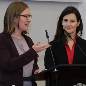 Zwei Frauen stehen am Rednerpult und sprechen.
