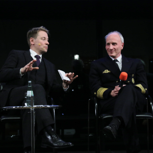 Moderator und Vizeadmiral diskutieren.