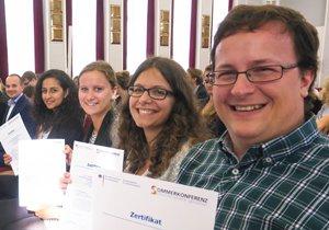 Während der Schlusszeremonie der Sommerkonferenz zeigen vier Teilnehmer, die in erster Reihe des gefüllten Hörsaals sitzen, ihre Zertifikate