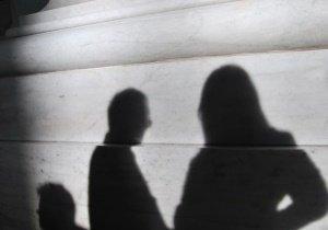 Das Bild zeigt Schatten von Personen vor einer grauen Wand.