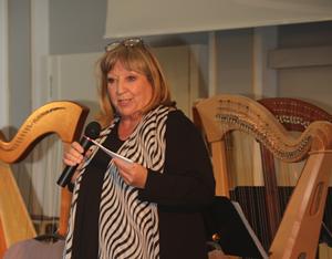 Die Sängerin Angelika Mann steht im Historischen Saal der BAKS mit einem Mikrofon in der Hand vor zwei Harfen und spricht zum Publikum.