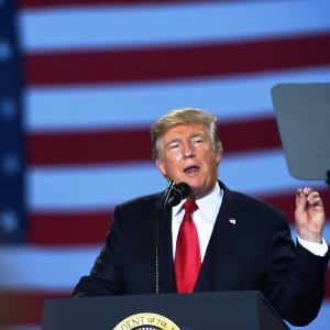 Donald Trump spricht an einem Rednerpult, hinter ihm ist die Flagge der Vereinigten Staaten erkennbar.