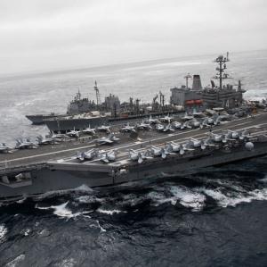 Ein Flugzeugträger mit mehreren Flugzeugen an Bord ist im Meer zu sehen.