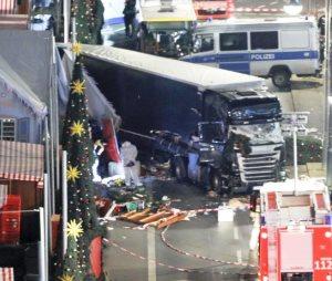 Ein LKW ist in die Buden eines Weihnachtsmarktes gekracht, man sieht einen Weihnachtsbaum auf der rechten Bildhälfte.