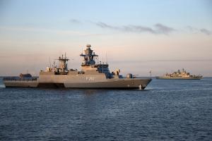 Zwei Kriegsschiffe fahren in mittlerem Abstand zueinander parallel langsam durch ruhige See.
