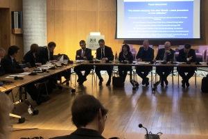 Zahlreiche geschäftlich gekleidete Menschen sitzen an einem karreeförmig aufgestellen Konferenztisch