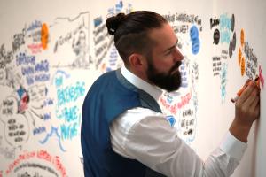 Ein Mann malt mit bunten Filzstiften eine Leinwand an.