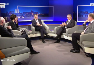 """In einem Fernsehstudio des Senders """"phoenix"""" diskutiert der Moderator der Sendung mit den Talkshowgästen."""