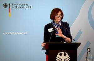 Bettine Cadenbach steht an einem schwarzen Rednerpult mit Bundesadler darauf vor einer blauen Wand mit dem Logo der BAKS und spricht in ein Mikrofon.