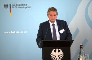 Rüdiger Huth steht an einem schwarzen Rednerpult mit Bundesadler darauf vor einer blauen Wand mit dem Logo der BAKS und spricht in ein Mikrofon.