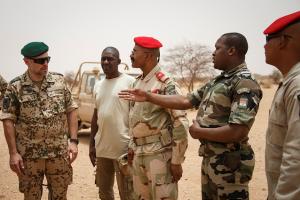Nigerische und internationale Soldaten reden miteinander.