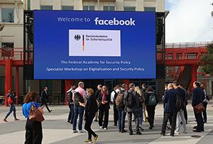 Eine Gruppe von Menschen steht vor einem Gebäude mit einer großen Videowand daran, die das Logo von Facebook und jenes der BAKS zeigt.
