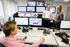 Ein Mann sitzt an einem Computer mit zahlreichen Bildschirm; dahinter stehen zwei weitere Männer, und an der Wand hängen weitere Bildschirme.
