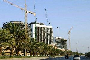 Links von einer breiten Autoverkehrsstraße ragen hinter einer dichten Reihe von Palmen im Bau befindliche Hochhäuser und Baukräne auf.