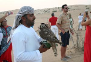Das Bild zeigt einen arabishen Falkner, der mit westlich gekleideten Menschen in der Wüste steht.