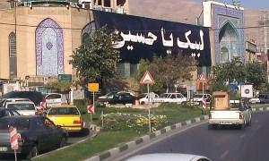 Im Vordergrund zeigt das Bild dichten Autoverkehr, im Mittelgrund ragen Geäbude im islamischen Baustil auf, daran ist ein sehr großes Banner mit Aufschrift in Persisch befestigt; im Hintergrund bildet ein Gebirgskamm den Horizont.