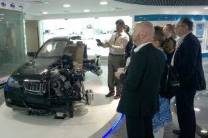 Ein Mann steht neben einem teilweise aufgeschnittenen modernen Pkw, der Einblick in die Fahrzeugtechnologie gewährt; zahlreiche Personen schauen den Pkw an.