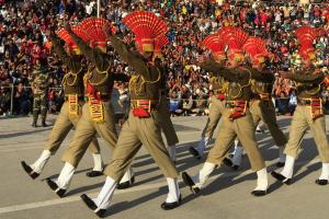 Uniformierte Soldaten mit auffälligen fächerartigen Kopfbedeckungen marschieren im Stechschritt vor einer mit Publikum besetzten Tribüne.