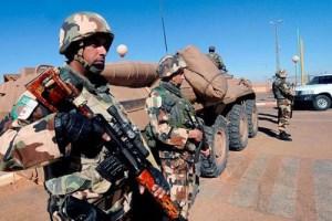 Zwei Soldaten stehen bewaffnet an einem gepanzerten Fahrzeug.
