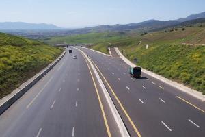 Eine sechsspurige Autobahn führt durch eine steppenartige Landschaft; wenige Autos sind darauf zu sehen..