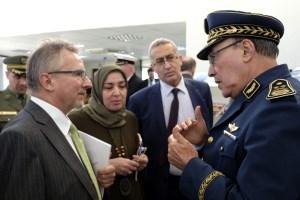 Ein Mann in geschäftlicher Kleidung und ein Mann in Uniform sprechen miteinander; im Hintergrund stehen ein weiterer Mann und eine Frau.
