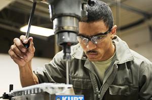 Ein Mann mit Schutzbrille und Arbeitskleidung bedient eine in einen Ständer eingespannte Bohrmaschine und blickt konzentriert auf das zu durchbohrende Werkstück.