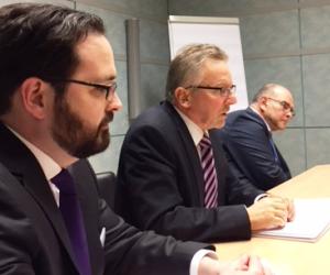 Drei geschäftlich gekleidete Männer sitzen an einem Konferenztisch und sprechen miteinander.