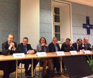 Sieben geschäftlich gekleidete Personen sitzen an einem Konferenztisch und hören aufmerksam zu.