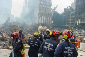 Zahlreiche uniformierte Personen mit Schutzkleidung blicken auf staubbedeckte Trümmer des World Trade Centers in New York City.