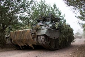 Ein getarnter Panzer fährt durch den Wald.