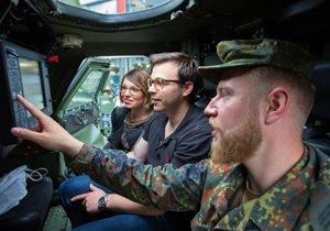 Ein Soldat in einem Militärfahrzeug erklärt zwei Besuchern eines Aktionstags der Bundeswehr in Trier am 12. Mai 2016 die Funktionsweise von Geräten über dem Fahrersitz.