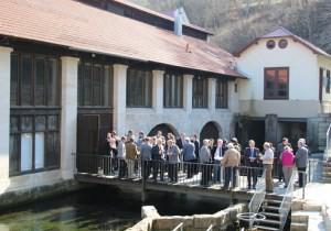 Eine Menschengruppe im Gespräch steht auf einer Brücke, die über einen alten Mühlgraben in das Gebäude der Hammerschmiede in Königsbronn führt.
