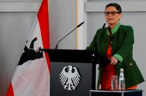 Eine Frau spricht an einem Rednerpult, das ein Bundesadler ziert. Im Hintergrund ist die deutsche Fahne Berlins erkennbar.