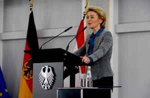 Eine Frau spricht an einem Rednerpult, das ein Bundesadler ziert. Im Hintergrund ist die deutsche Fahne aufgestellt, die Fahnen Europas und Berlins ebenfalls erkennbar.