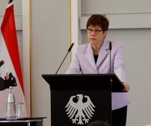 Annegret Kramp-Karrenbauer steht sprechend an einem Rednerpult mit dem Bundesadler darauf.