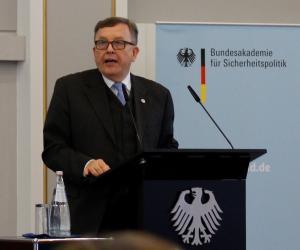 Armin Staigis steht sprechend an einem Rednerpult mit dem Bundesadler darauf; rechts von ihm ragt ein Aufsteller der BAKS auf.