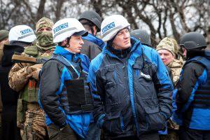 Das Foto zeigt mehrere uniformierte Angehörige der OSZE-Beobachtermission in der Ukraine und mehrere bewaffnete und zum Teil vermummte Soldaten. Zwei der Beobachter schauen sich um, während ihnen ein Vermummter über die Schulter schaut.