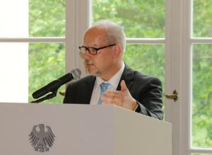 Andreas Backhoff steht vor einem Fenster mit grünem Laubwerk im Hintergrund hinter einem weißen Pult mit dem Bundesadler in Anthrazit darauf und spricht gestikulierend in ein Mikrofon.