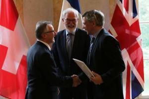 Drei Männer stehen vor den drei Nationalflaggen der Schweiz, Frankreichs und Großbritanniens; der linke der drei übergibt an den rechten eine Mappe mit einer Urkunde.