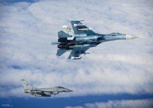 Ein britisches Kampfflugzeug und ein russisches Kampfflugzeug fliegen in großer Nähe zueinander über einer geschlossenen Wolkendecke.