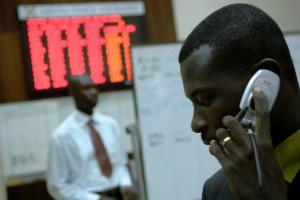 Das Foto zeigt zwei afrikanische Männer, einer in kaufmännischer Kleidung im Hintergrund stehen vor einer Digitalanzeige von Börsenkursen, einer im Vordergrund mit einem Mobiltelefon am Ohr.