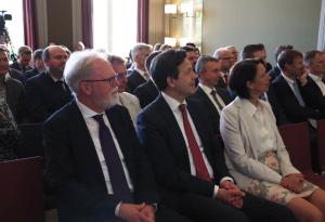In einer ersten Stuhlreihe sitzen der Vizepräsident der BAKS Thomas Wrießnig, der Direktor des GCSP Christian Dussey und die Botschafterin der Schweiz in Deutschland Christine Schraner Burgener; dahinter sitzen zahlreiche andere Personen in Stuhlreihen.