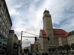 Rechts im Bild ragt das steingemauerte Rathaus Neukölln mit seinem Turm auf, links die Wand eines mehrstöckigen modernen Gebäudes; in der Mitte ist eine breite Straße erahnbar und eine Verkehrsampel, auf der zahlreiche Tauben sitzen, sichtbar.