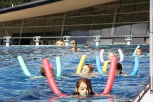 Mehrere Kinder schwimmen mit langen dünnen zylindrischen bunten Schwimmhilfen in einem Schwimmbecken; im Hintergrund ragt hinter Schwimmstartblöcken die Glasfassade des Schwimmbads auf.