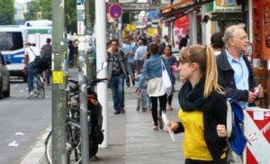 Zahlreiche Menschen stehen und gehen entlang einer Einkaufsstraße in Berlin-Neukölln.