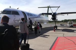 Mehrere Menschen steigen in ein Flugzeug ein.