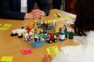 Zwei erwachsene Menschen in geschäftlicher Kleidung beschäftigen sich an einem Tisch mit Legosteinen.