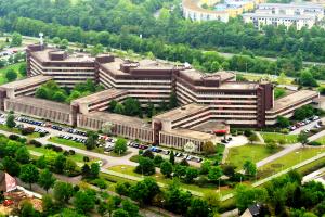 Ein dunkelbraunes Bürogebäude, aus der Vogelperspektive betrachtet, steht inmitten von Grünanlagen.